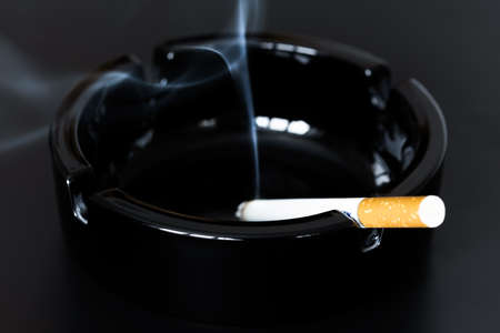 Reeky cigarette in a black glass ashtray on a dark background. Stock Photo