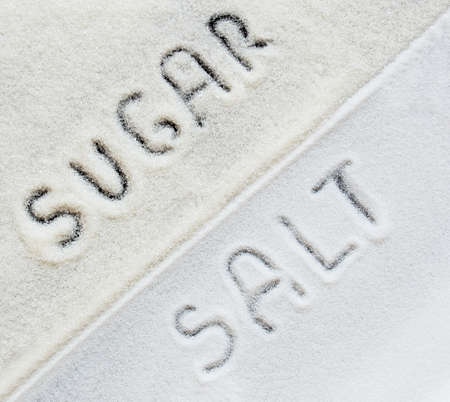 Scattered salt and sugar, divided diagonally with the inscription Sugar and Salt