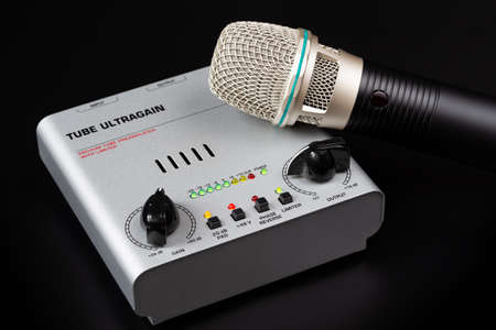Tube preamp and microphone on a dark background.