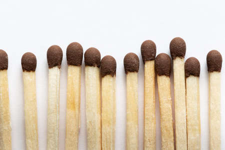 Wooden matches with brown heads, closeup on a light background Stock Photo