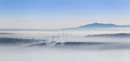 Power transmission towers in a fog, in a mountainous region in southern Yakutia, Russia.