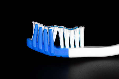 Closeup of two-tone modern toothbrush on a dark background