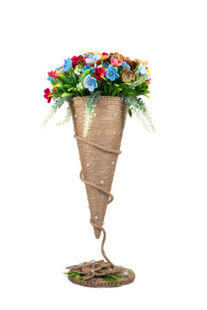 Decorative knitted flowers in a conical vase on a white background isolated. Handwork, hobby. Reklamní fotografie