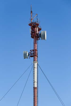 Mast with radio relay antennas against a blue sky