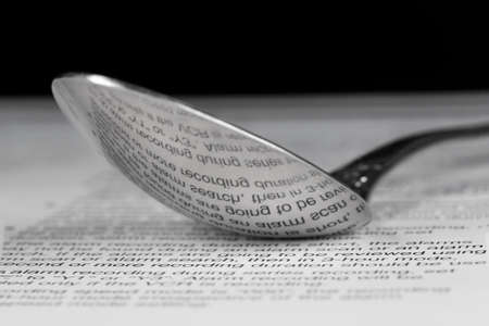 Reflection of printed text on the back of a steel spoon