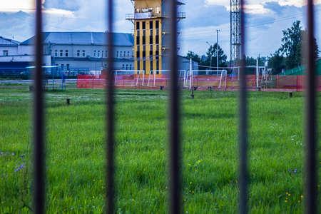 een voetbalveld met groen gras in de avond met metalen staven Stockfoto