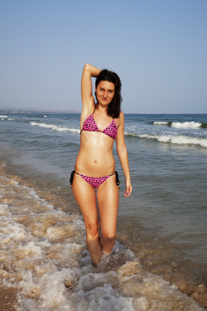 woman in swimsuit walking on the beach photo