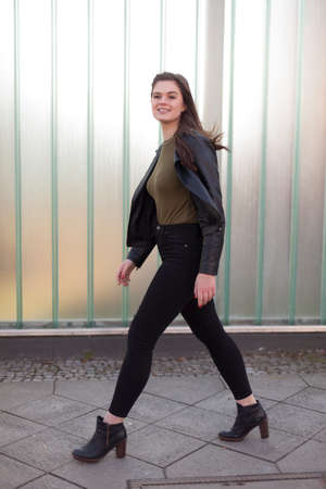 Junge Frau, die auf einen Bürgersteig geht Standard-Bild