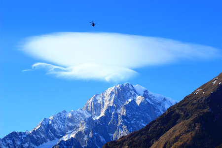 courmayeur: Rescue helicopter in flight, Mont Blanc peak with lenticularis cloud above in background