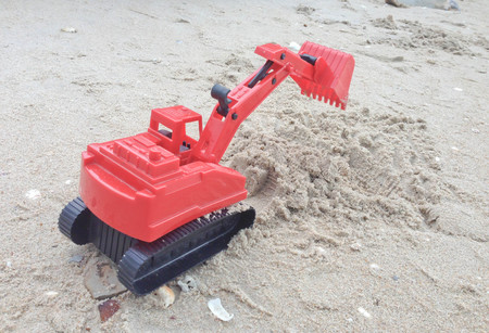 industrail: Childrens toy red excavator car on sand,industrail symbols Stock Photo