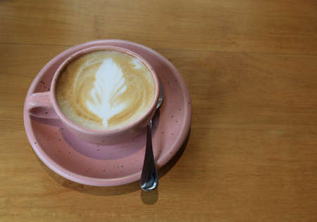 Hot latte art coffee in pink cup on wooden table with copyspace