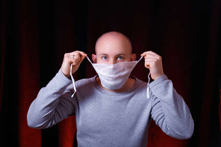 A man tying a medical gauze mask on dark red background. Emotion of surprise. Virus preventive methods. Protection of upper and lower respiratory system from  Chinese coronavirus concept.