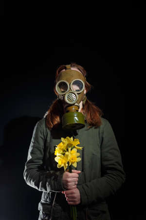 Girl in gas mask with flowers in hands. Enviromental pollution, nature protection, ecology disaster and hope concept. Black background, copy space.