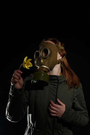Girl in gas mask with flower in hands. Enviromental pollution, nature protection, ecology disaster and hope concept. Black background, copy space.