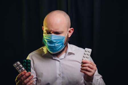 Frowned man in gauze mask and white shirt holding medicines in hands on dark background. Healthcare, respiratory illness prevention, prophylaxis of virus infections, COVID-19 concept.