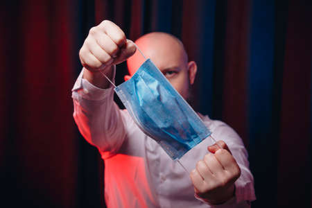 Man in white shirt holding gauze mask in hands on dark background. Emotion of assertiveness and determination. Healthcare, respiratory illness prevention, prophylaxis of virus infections, COVID-19 concept.