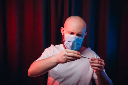 Man in gauze mask holding thermometer and checking fever sympthom. Emotion of fear and doubt. Healthcare, respiratory illness prevention, prophylaxis of virus infections, COVID-19 concept.