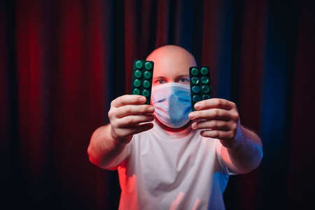 Man or doctor in gauze mask holding  medicines. Emotion of determination. Healthcare, respiratory illness prevention, prophylaxis of virus infections, COVID-19 concept. 免版税图像