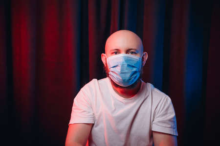 Patient or doctor in gauze mask on dark red and blue background. Emotion of calm and tranquility. Healthcare, respiratory illness prevention, prophylaxis of virus infections, COVID-19 concept. 免版税图像