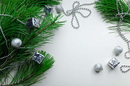 Christmas holiday background - decoration on a white table background. New year pine and silver Christmas balls. Top view. Place for text. 免版税图像