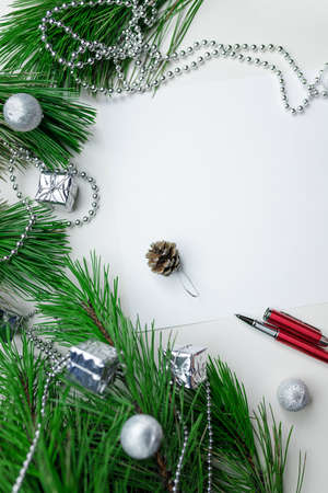Christmas holiday background - decoration on a white table background with blank white sheet and red pen. New year pine and silver Christmas balls. Top view. Place for text. 免版税图像