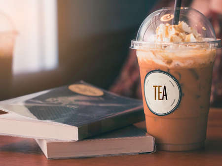 Milk Tea on wooden table with books to read.