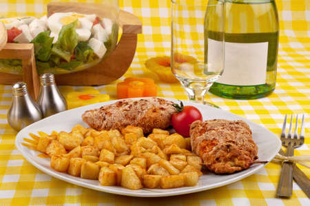 Chicken breast with fried potatoes and salad on a beautiful spring looking table setting photo