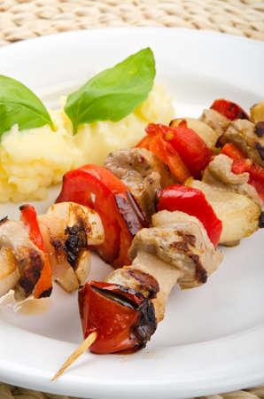 Meat and vegetables skewers with potatoes on white plate photo