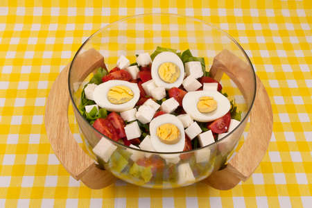 Fresh salad with eggs in a nice glass and wood bowl photo