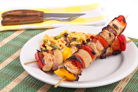 Meat and vegetables skewers with rice on a plate photo