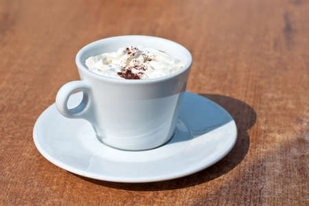 Photo of a cappuccino cup on wooden table photo
