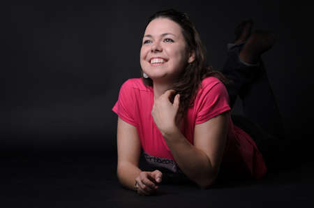 red shirt: The girl in the red shirt lying on the floor. The girl smiles. Black background