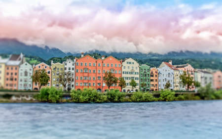 Colored houses on the bank of the Inn river in Innsbruck, slightly blurred at the edges