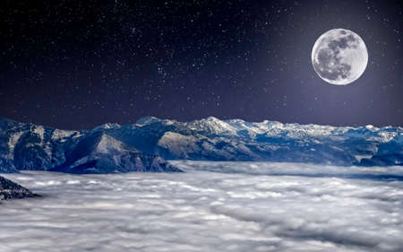 The full moon over snowy Alps  in the night, above clouds, under the starry sky
