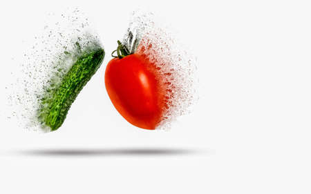 Tomato and cucumber exploding (dispersing) on white background