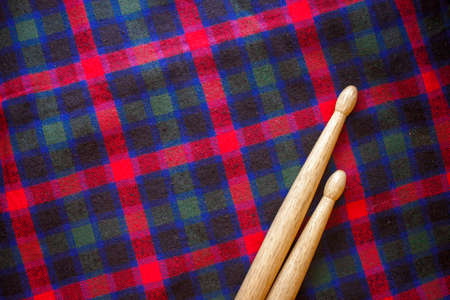 Two drum sticks of oak for rock and roll  lie on the fabric of a Scottish cage textile