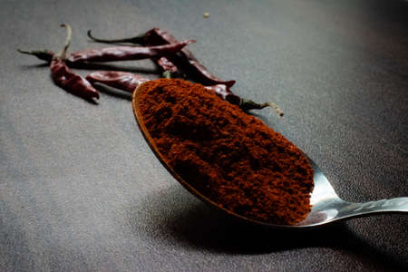 Indian Garam masala powder in bowl and it's ingredients colourful spices. Served over moody background. selective focus