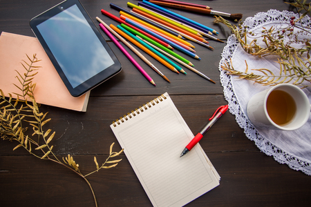 color pencils: Notebook with squared paper on the dark wooden table with cup of tea, color pencils, pad, orange book and dry plants