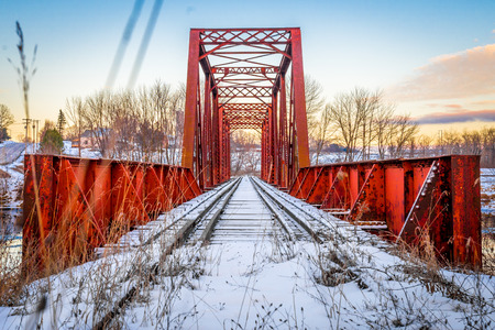 Red Rusty Train Bridge over Snow Icy River