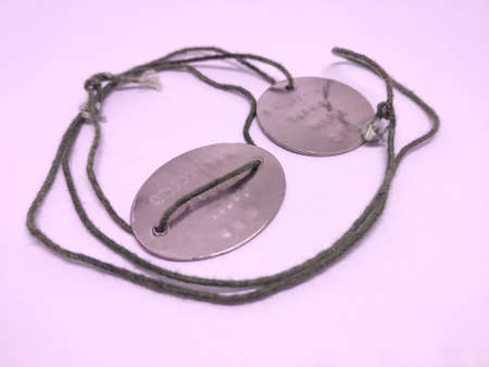 Old rounded soldier dog tags with rope.