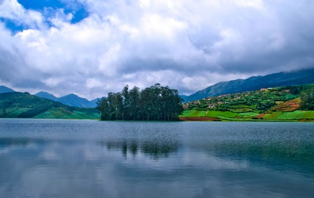 Beautiful blue pristine lake and meadows surrounded by hills photo