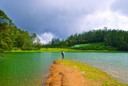 Lady n kid enjoying the pristine lake surrounded by hills photo