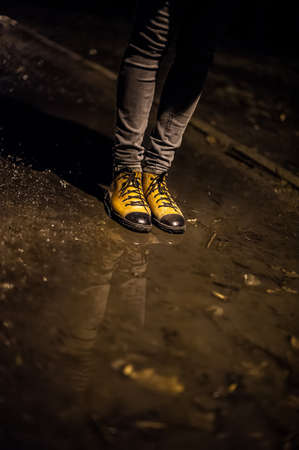 lonelyness: Girl legs in yellow and black retro shoes. near lantern at night with reflection in water