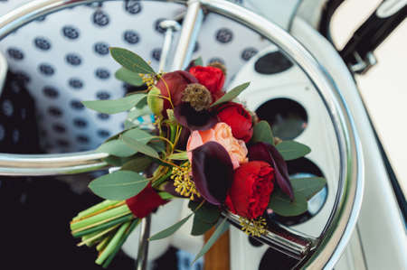 wedding bouquet made of red and biege peony on a chrome wheel of retro car