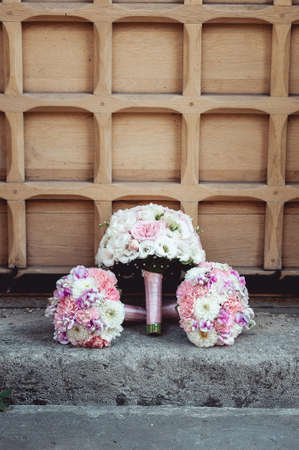 three wedding bouquets of white and biege roses on the floor.