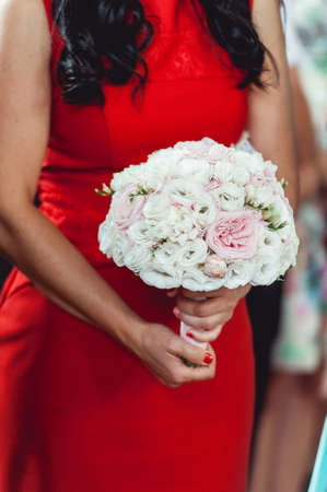 woman in a red dress holds wedding bouquets of white and biege roses