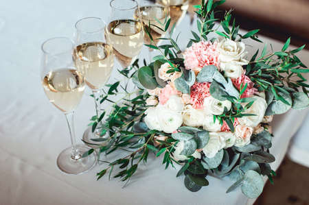 wedding bouquet of white and biege with a ribbon on the table with six glasses of champagne Stock Photo