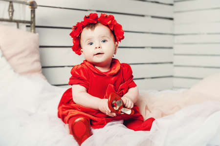 cute little baby in a red dress and a red wreath on her head