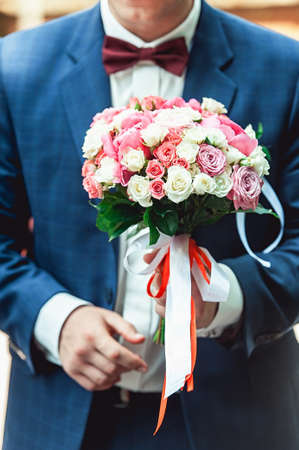 fiance in a dark blue suit holds a wedding bouquet made of roses