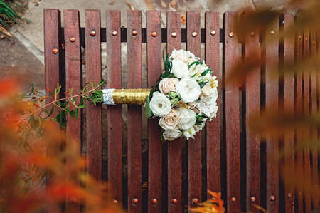 bridal bouquet of white roses with a gold ribbon on a brown bench